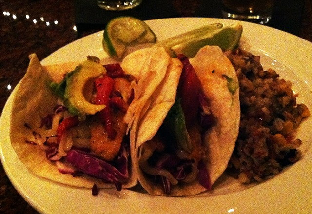 Fish tacos with avocado, roasted red pepper and cabbage.